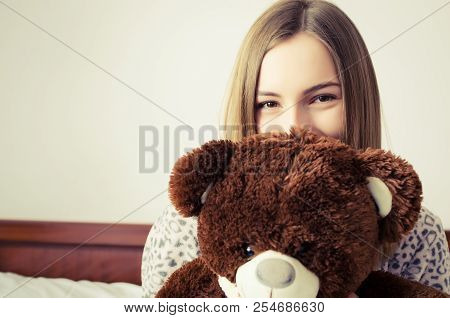 Happy Young Woman With Blonde Hair In Embrace With A Stuffed Animal Toy. Favorite Brown Teddy Bear I
