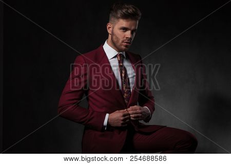 elegant man buttoning his red suit and sitting on a wooden chair on grey wallpaper background