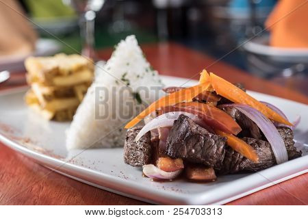 Peruvian Food Lomo Saltado :a Salted Beef With Tomatoes, Onion, Fried Potatoes And Rice. On A White