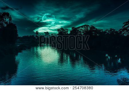 Beautiful Landscape Of Night Sky And Full Moon Behind Partial Cloudy Above Silhouettes Of Trees At R