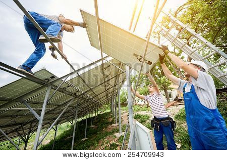 Stand-alone solar photo voltaic panel system installing. View from below of three technicians workers mounting heavy solar panel. Alternative energy production and professional construction concept. poster