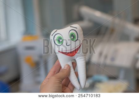 Smiling Tooth In Female Hand On Dentist Office Background.tooth Smiling.white Healthy Teeth Model.de
