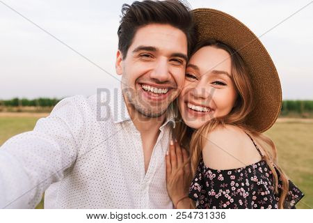 Lovely smiling couple man and woman dating, and taking selfie together while walking outdoor through field