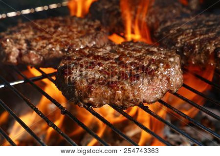 Close Up Beef Or Pork Meat Barbecue Burgers For Hamburger Prepared Grilled On Bbq Fire Flame Grill,