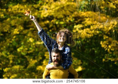 Couple In Love Walks In Autumn Park. Man And Woman With Happy Faces On Natural Background. Girl And