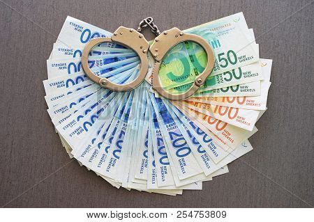 Handcuffs On The Background Of Israeli Money. The New Israeli Money Bills (banknotes) Of 50, 100 And