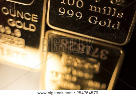 Fine solid gold 999.9 one ounce bullion ingot precious metals bar closeup isolated photo. poster