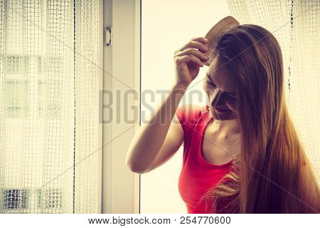 Haircare, morning routine concept. Woman sitting on windowsill brushing her long dark hair with comb. poster