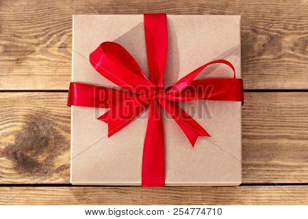 Crafted Box With A Gift.  Vintage Gift Box On Old Wooden Background. Gift Parcel Box With Ribbon Bow