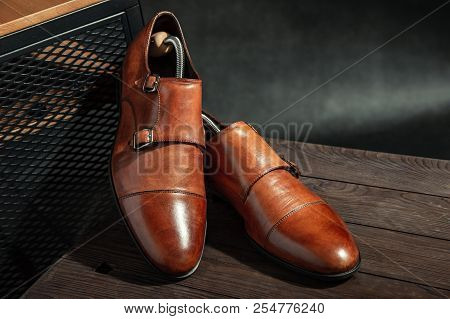 Elegant Brown Monk Shoes With Double Strap On A Wooden Table
