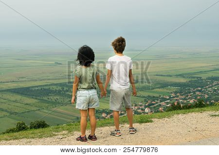 Kids Holding Hands On The Hill Panorama. Kids Looking On Panorama From Mountain Peak. Kids Holding H
