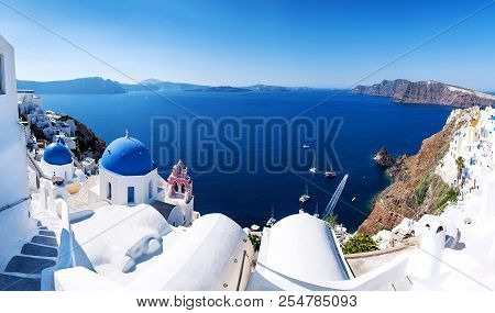 Panoramic View With Greek Orthodox Church With Blue Domes And Sea In Oia In Santorini, Greece, Europ