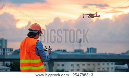 Young Asian engineer man flying drone over construction site during sunset. Using unmanned aerial vehicle (UAV) for land and building site survey in civil engineering project. poster