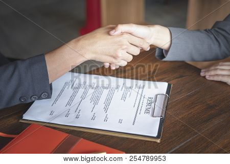 Handshake Success Job Interviewing. Job Applicant Having Interview. Shaking Hand With Resume On Desk