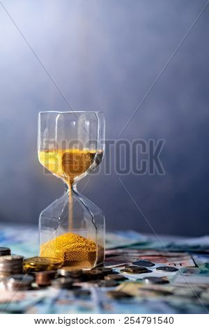 Sand running through the shape of hourglass on table with banknotes and coins of international currency. Time investment and retirement saving. Urgency countdown timer for business deadline concept poster