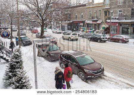 Montreal, Ca - 17 December 2016: Snowstorm In Montreal. Pedestrians On St-denis Street.