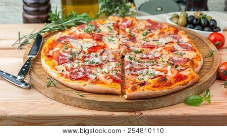 Thick Italian Pizza With Salami On A Wooden Tray With Tomotos Surrounded By Ingredients