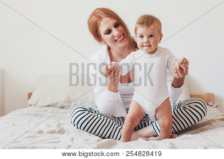 Portrait of beautiful loving mom playing with her 8 months old baby in bedroom, making first steps together