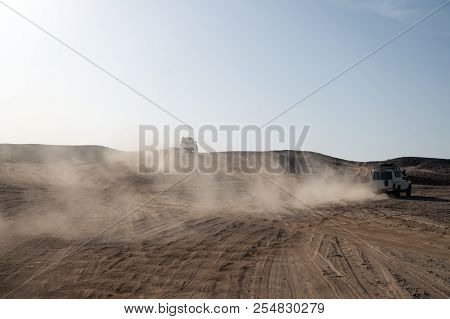 Competition Racing Challenge Desert. Car Overcome Sand Dunes Obstacles. Car Drives Offroad With Clou