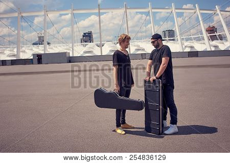 Musicians With Musical Instruments In Cases Having Conversation While Standing On Street