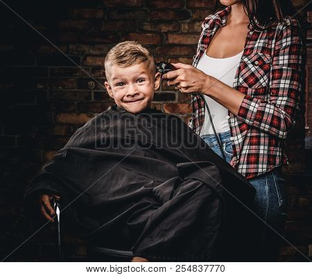 Funny Preschooler Boy Getting Haircut. Children Hairdresser With The Trimmer Is Cutting Little Boy I