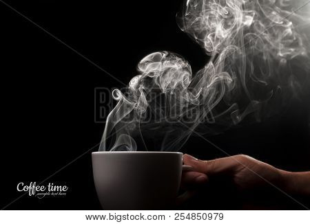 Fragrant coffee on a black background for your advertising. Cup of coffee in his hand. Smoke from hot coffee.