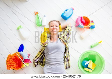 Woman in protective gloves is smiling and wiping dust using a spray and a duster poster