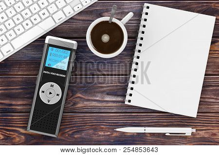 Journalist Digital Voice Recorder Or Dictaphone, Keyboard, Blank Note Pad With Pen And Cup Of Coffee