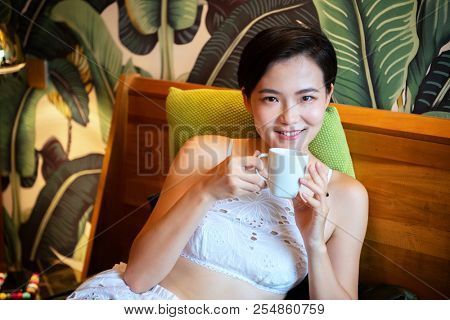Beautiful chinese young woman wearing pajamas lies in bed and drinks coffee. Lazy morning. Happy sleppy girl wit cup og tea in bedroom.