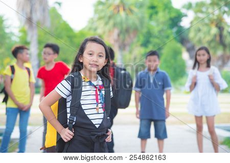 Young Asian Girl Standing In Park And Smiling At Camera