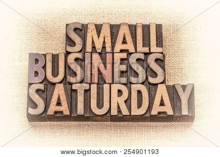 Small Business Saturday word abstract - text in vintage letterpress wood type against burlap canvas, sepia toned image - holiday shopping concept