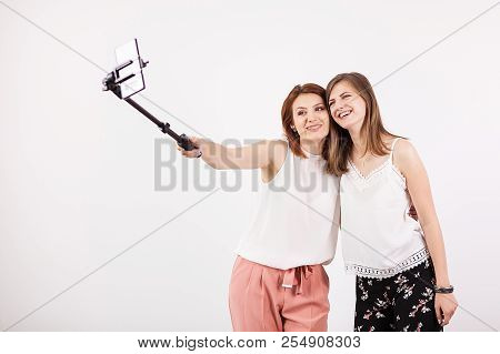 Two Beautiful Young Woman Taking A Selfie With A Selfie Stick