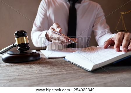 Male Lawyer Working With Lawsuit Papers On Tabel In Courtroom