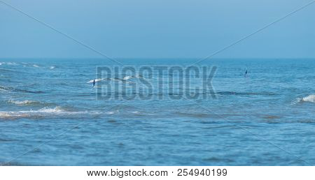 Rough Waves On A Beautiful Blue Sea On A Summer, Sunny And Windy Day. Protruding Warning Flags From