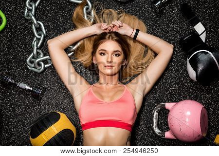 Portrait Of Fit Brutal Athletic Young Cute Lady In Fashion Sportswear Laying Near Weights And Fitnes