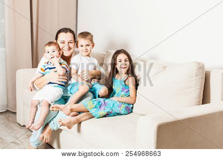 A Woman With Children Are Sitting On The Couch.