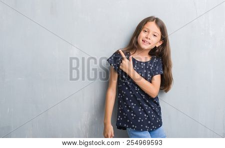 Young hispanic kid over grunge grey wall cheerful with a smile of face pointing with hand and finger up to the side with happy and natural expression on face looking at the camera.
