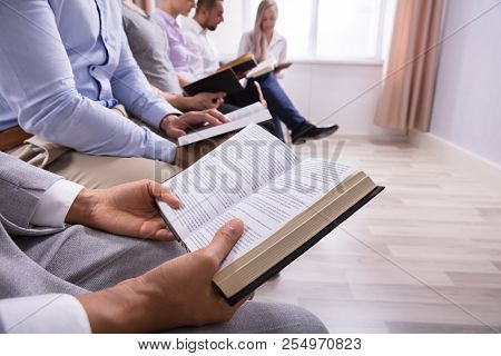 Mid Section View Of People Reading Holy Book In Hall