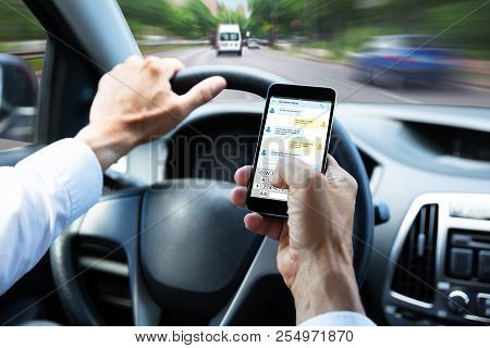 Man Typing Text Message On Mobile Phone While Driving Car