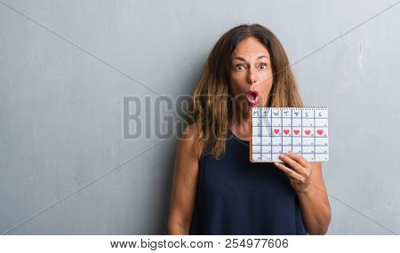 Middle age hispanic woman standing over grey grunge wall holding period calendar scared in shock with a surprise face, afraid and excited with fear expression