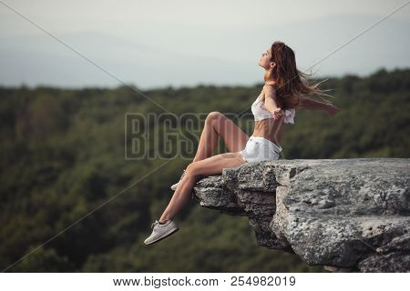 Beautiful Woman Sitting On The Rock Cliff With Hands Raised And Enjoy The Nature And Freedom