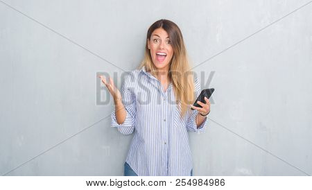 Young adult woman over grey grunge wall looking at smartphone texting a message very happy and excited, winner expression celebrating victory screaming with big smile and raised hands