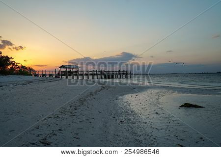 Brilliant Sunset At Sanibel Pier Along Sandy Beach On Sanibel Island In Florida