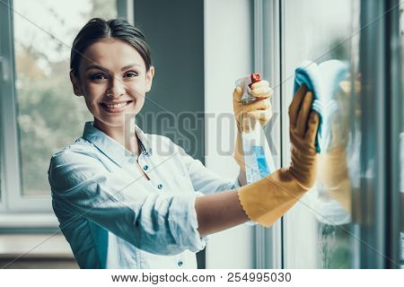 Young Smiling Woman Washing Window With Sponge. Happy Beautiful Girl Wearing Protective Gloves Clean