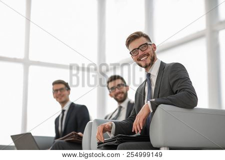 young successful businessman on background of office.