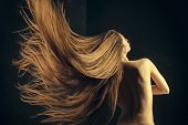 Hairdresser and barber. Haircare and shampoo. Woman with stylish long hair and naked back. Girl has no makeup and healthy hair on black background. Beauty salon and fashion. poster