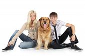 A young family with a dog breed golden retriever sitting on floor looking at camera poster