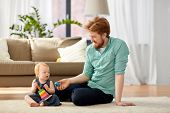 family, fatherhood and people concept - happy red haired father with ball playing with little baby daughter at home poster