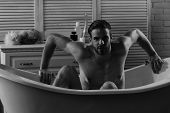 Macho sitting naked in bathtub, selective focus. Guy in bathroom with toiletries on background.  Man with beard and seductive face. Sex and erotica concept. poster