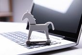 Close-up Of Trojan Horse Icon On Laptop Keypad poster